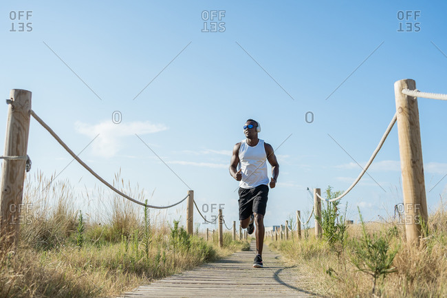 Low angle full body of strong muscular African American male athlete in headphones and running in countryside
