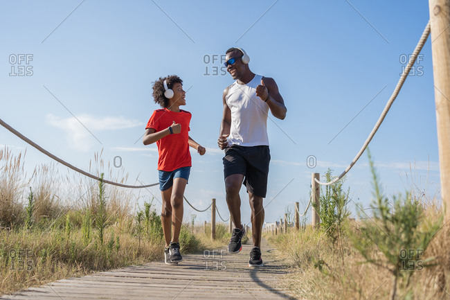 Low angle full body of cheerful active African American dad and son in sportswear and headphones jogging along fenced way while training together in sunny summer day in countryside
