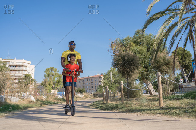 Full body of cheerful young African American man with son in sportswear and headphones riding scooter together in urban park in summer day
