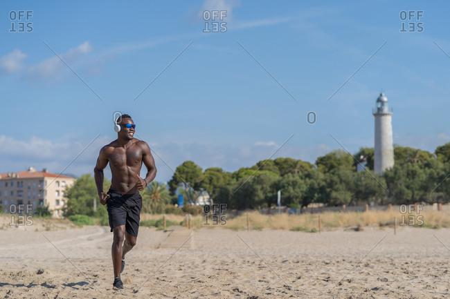 Full body shirtless muscular African American man in headphones and sunglasses jogging on sandy shore near waving sea during workout in sunny day
