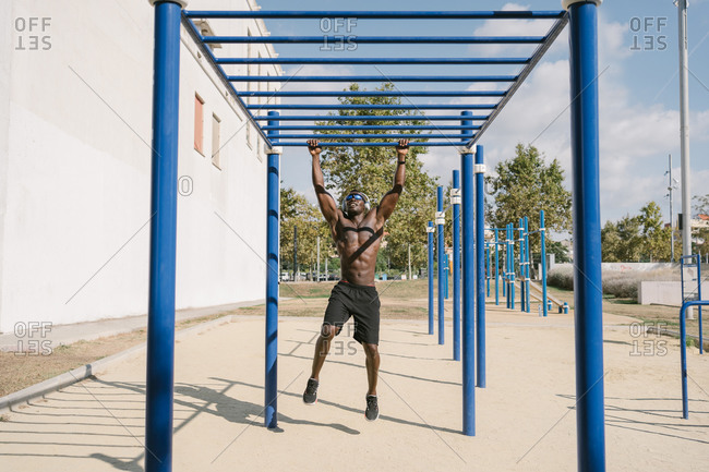 Full length of shirtless athletic African American male doing exercise on fitness equipment while training alone on sports ground
