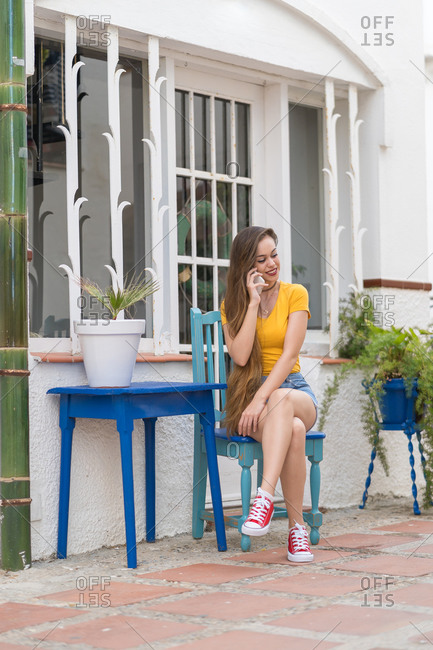 Young female millennial in trendy wear sitting at table in outdoors cafe and chatting with friend on social media