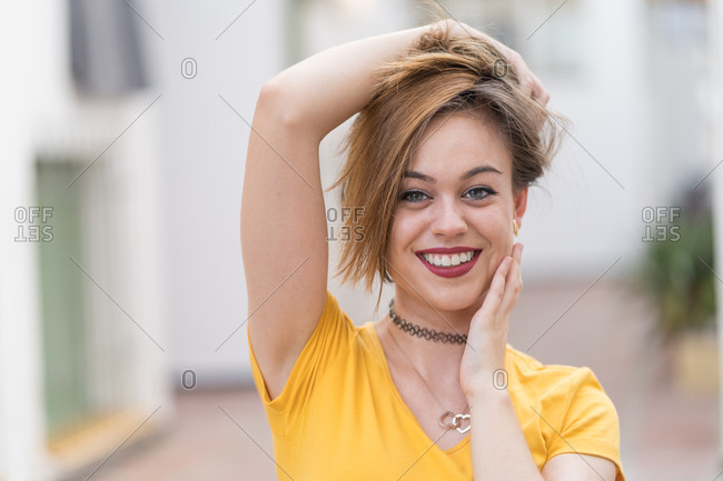 Satisfied female millennial with long hair standing on street and looking at camera while enjoying stroll during weekend