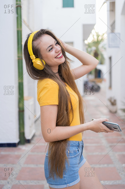 Trendy female millennial on street and choosing songs from playlist on smartphone for listening to music in headphones