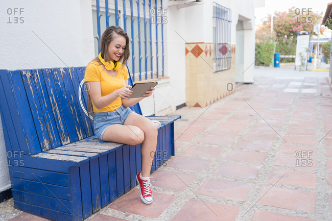 Delighted female millennial in trendy wear relaxing on bench in city and watching funny videos on tablet