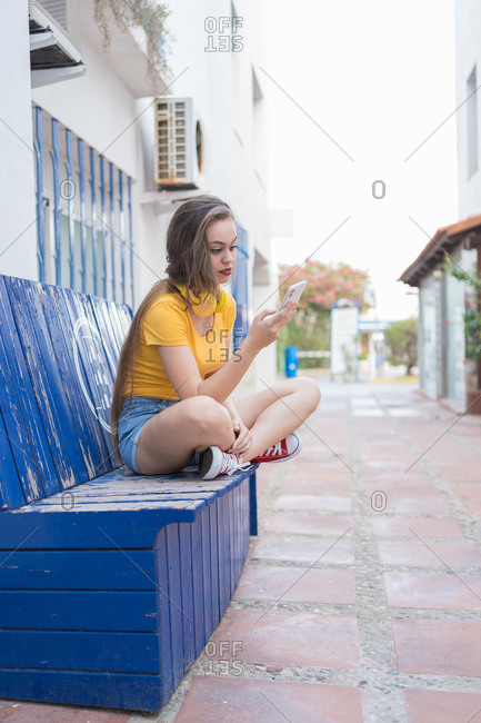 Trendy female millennial sitting on shabby bench on street and choosing songs from playlist on smartphone for listening to music in headphones
