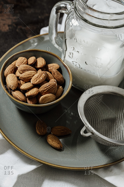 From above ceramic bowl with fresh almonds placed on plate near bottle of vegan milk and strainer