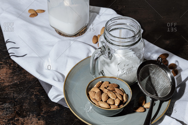 Bowl of natural almonds placed near glass jar of fresh vegan milk on plate and napkin in dark room