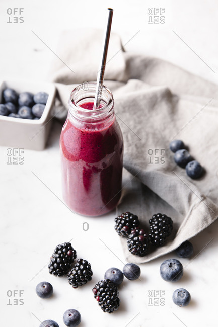 Glass bottle with fresh homemade berry smoothie and a reusable metal straw. Some berries near the bottle on a marble surface. High angle vertical image.