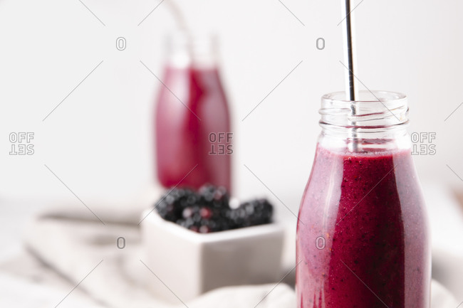 Crop shot of a glass bottle containing pink homemade berry smoothie, with a metal straw.