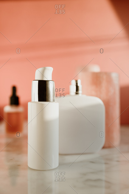 Glass dropper flask with skincare serum placed near spray bottle and other containers with cosmetic products on marble table against pink wall