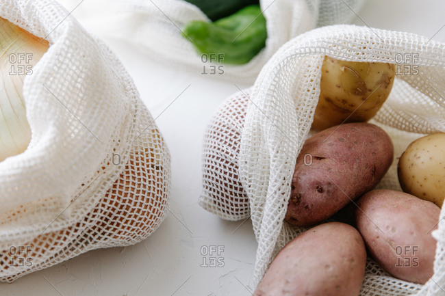 Closeup of raw potatoes in eco friendly fabric bags placed on table in kitchen