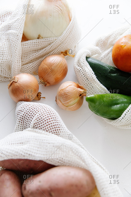 High angle of fresh onions in eco friendly textile bags placed on table in kitchen