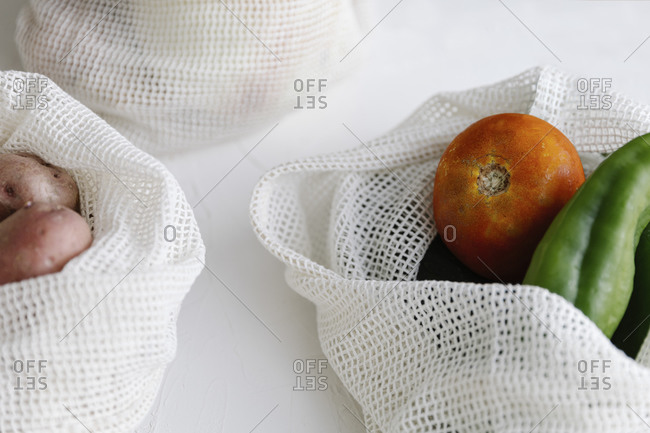Closeup of raw potatoes and peppers in eco friendly fabric bags placed on table in kitchen