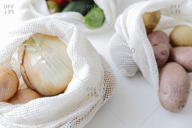 Closeup of raw potatoes and onions in eco friendly fabric bags placed on table in kitchen