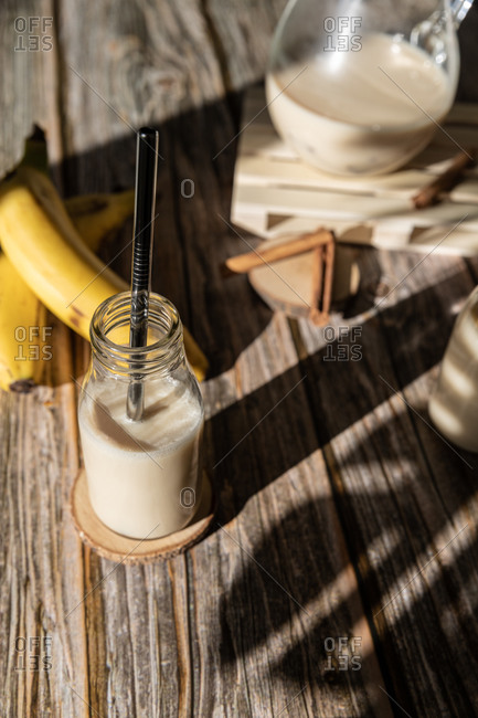 From above glass jar with healthy banana and cinnamon milkshake served on wooden table with ingredients