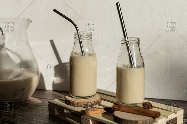 Glass bottles filled with healthy homemade sweet milkshake with cinnamon placed on wooden table against wall with shadow of monstera leaves