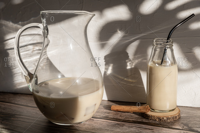 Side view of glass jar with healthy banana and cinnamon milkshake served on wooden table with ingredients