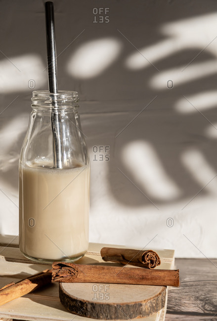 Glass bottle filled with healthy homemade sweet milkshake with cinnamon placed on wooden table against wall with shadow of monstera leaves