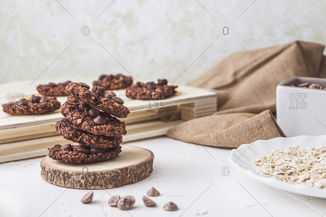 Still life shot of a stack of freshly oven baked oatmeal and banana chocolate chips over a wood trunk slice