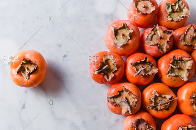 Top view of several ripe persimmons placed on marble table in bright modern kitchen