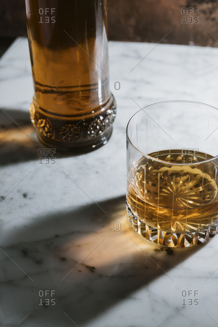 High angle of whiskey in glass and bottle arranged on marble table in bar
