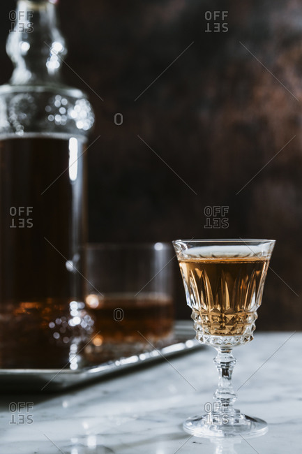 Side view of whiskey in glass and bottle arranged on marble table in bar