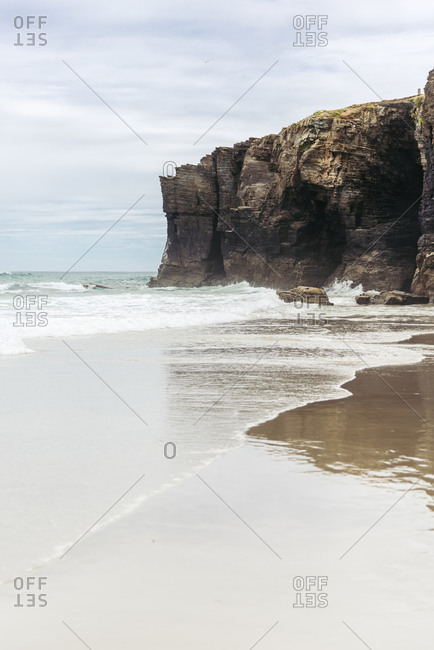 Majestic scenery of waving sea and rocky cliff on background of cloudy sky