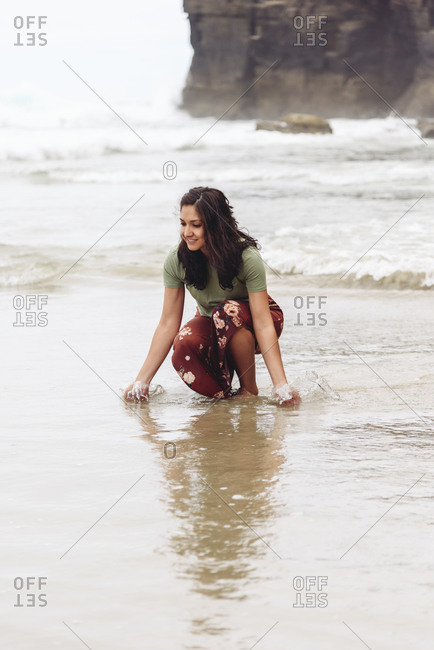 Delighted female traveler in wet clothes walking along seashore on background of rocky cliff