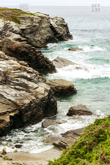 Scenic view of rough hills near sea with turquoise water on overcast day