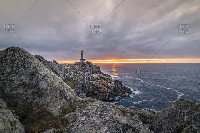 Spectacular scenery of lighthouse located on rough cliff near sea on background of sundown sky