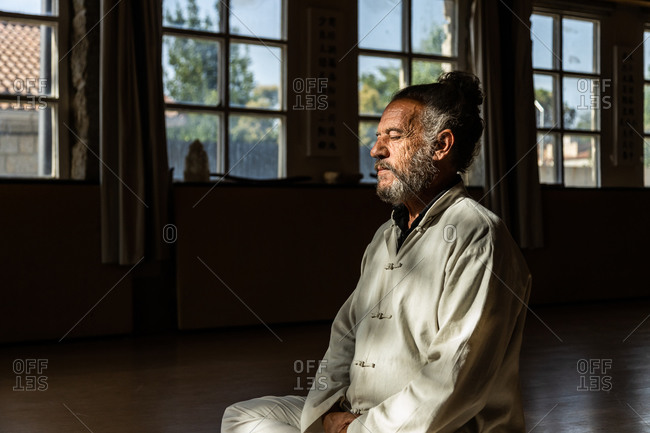 Crop of side view of focused bearded ethnic senior male practicing chi kung meditation in lotus position in dark studio