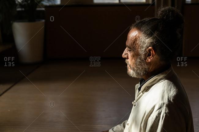 Crop of focused bearded ethnic senior male practicing chi kung meditation in lotus position in dark studio