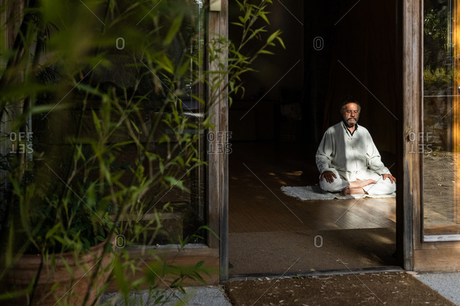 Full body front view of focused bearded ethnic senior male practicing chi kung meditation in lotus position in dark studio