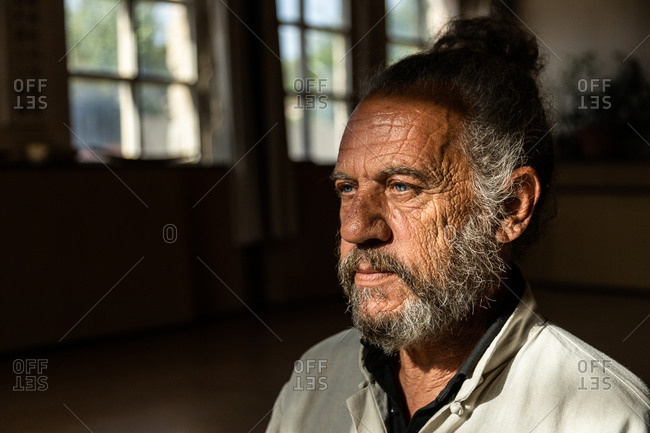 Serious elderly bearded ethnic male instructor of traditional chi kung or qigong looking away while standing in dark room