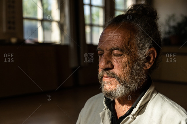 Serious elderly bearded ethnic male instructor of traditional chi kung or qigong with closed eyes while standing in dark room