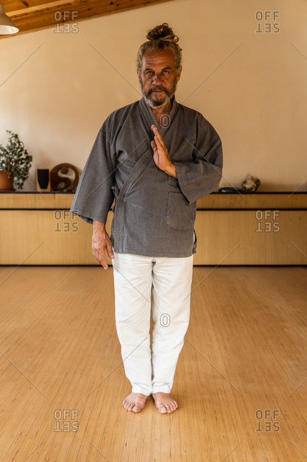 Senior bearded ethnic male chi kung practitioner in traditional wear looking at camera while standing in light studio