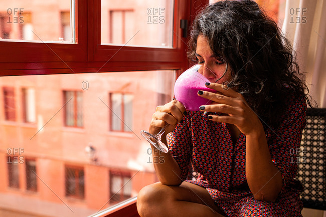 Ethnic thoughtful latin woman enjoying a healthy kefir and pitaya smoothie sitting by the windows at home