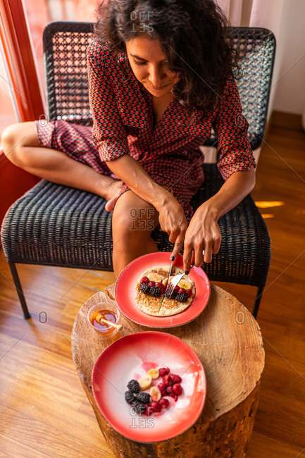 From above ethnic latin woman eating healthy breakfast almond flour pancakes with berries and honey