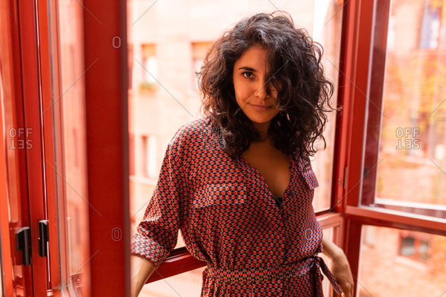 Beautiful ethnic latin woman leaning on windows of her apartment looking at camera