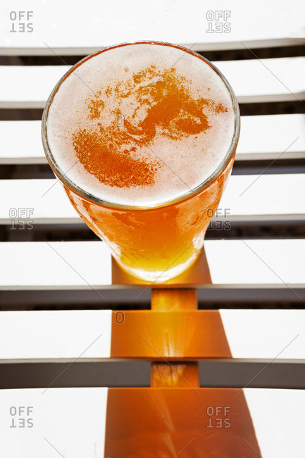 High angle of shiny glass with cool beer placed on wooden table in summer on sunny day for refreshment