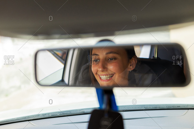 Young cheerful female driver sitting in modern automobile and reflecting in rearview mirror
