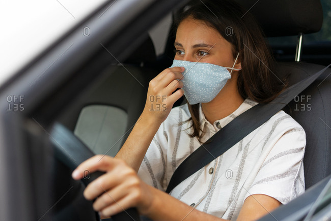 Content female driver in medical mask driving automobile in city during coronavirus epidemic