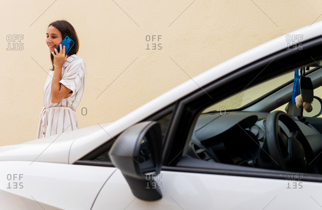 Side view of cheerful female driver standing on parking lot near modern automobile and having conversation on cellphone