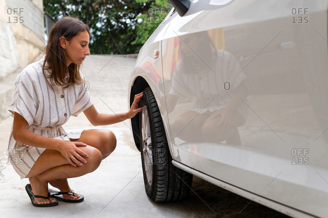 Side view of young female driver sitting near modern car and checking tires