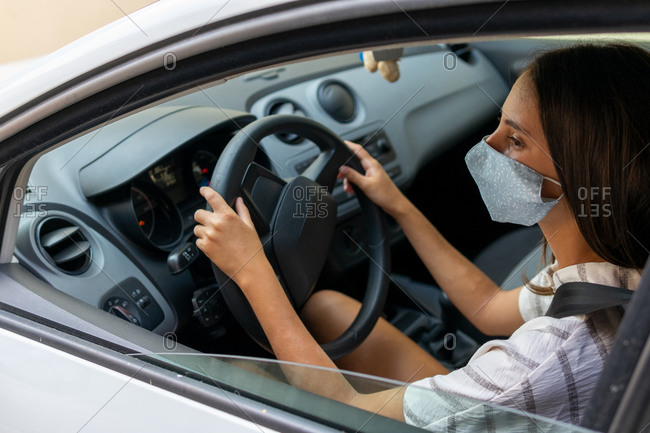 Side view of content female driver in medical mask driving automobile in city during coronavirus epidemic