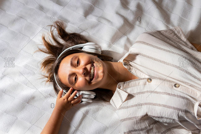 Crop child touching headphones of woman lying on bed in bedroom and enjoying listening to music while looking a camera
