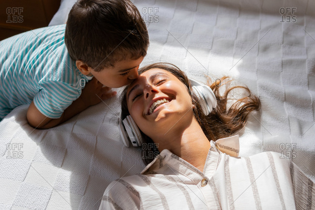 From above little son kissing forehead of happy young woman lying on bed and listening to music in headphones