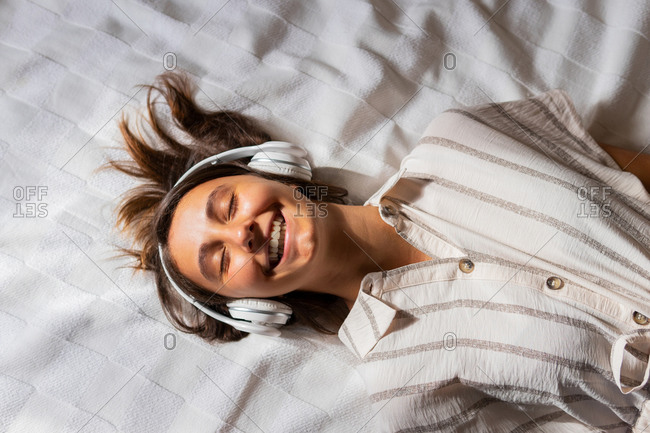 Crop child with headphones of woman lying on bed in bedroom and enjoying listening to music while with eyes closed