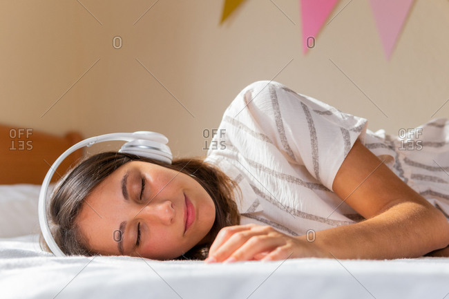 Young female with closed eyes lying on bed and listening to music on weekend day at home